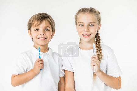 Photo for Kids holding toothbrushes and smiling at camera isolated on white - Royalty Free Image