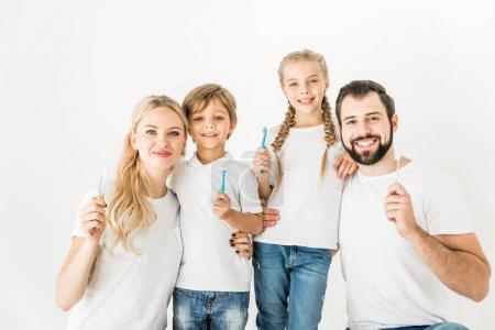 Photo pour Heureux famille tenant brosses à dents et souriant à la caméra isolé sur blanc - image libre de droit