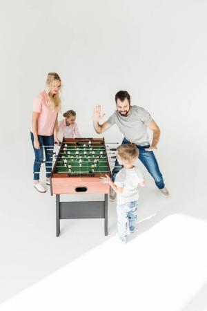Photo pour Famille heureuse avec deux enfants qui jouent ensemble isolé sur blanc de baby-foot - image libre de droit