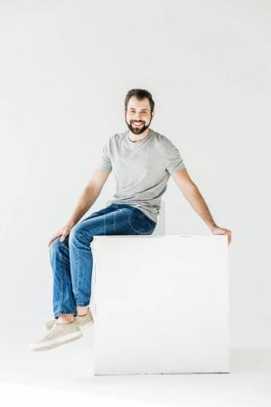 Photo for Happy handsome young man smiling at camera while sitting isolated on white - Royalty Free Image