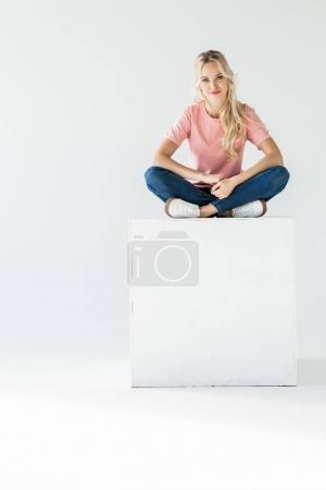 Photo pour Belle jeune femme assis et souriant à la caméra isolé sur blanc - image libre de droit