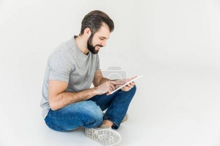 Photo pour Sourire barbu jeune homme utilisant tablette numérique tout en étant assis isolé sur blanc - image libre de droit