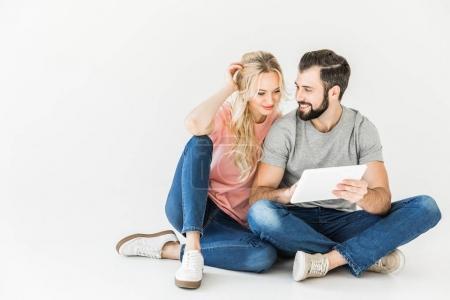 Photo pour Heureux jeune couple à l'aide de tablette numérique isolé sur blanc - image libre de droit
