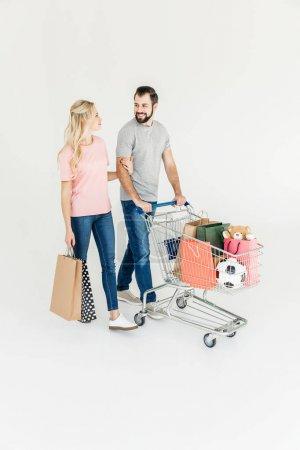 Photo pour Heureux jeune couple shopping ensemble et souriant mutuellement isolé sur blanc - image libre de droit