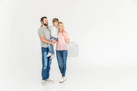 Foto de Felices padres con hijo juntos de pie y mirando a aislaron en blanco - Imagen libre de derechos