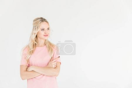 Photo for Beautiful smiling young woman standing with crossed arms and looking away isolated on white - Royalty Free Image