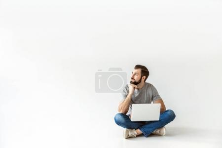Photo for Pensive bearded young man using laptop and looking away while sitting isolated on white - Royalty Free Image
