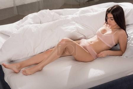 Photo for Attractive sensual girl posing in pink lingerie on bed - Royalty Free Image