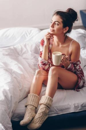 dreamy girl in knitted socks with coffee