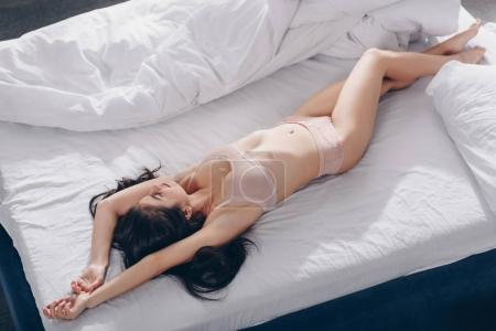 Photo for Attractive brunette girl in pink lingerie lying on bed - Royalty Free Image