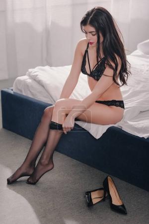 Photo pour Jolie fille sexy en lingerie noire, port de bas dans la chambre - image libre de droit