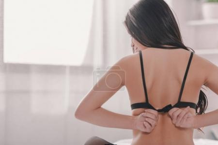 Photo for Back view of girl wearing black bra while sitting on bed in the morning - Royalty Free Image