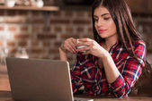 girl with laptop drinking coffee