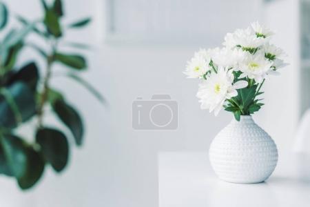 Photo pour Foyer sélectif de fleurs blanches dans un vase sur la table - image libre de droit