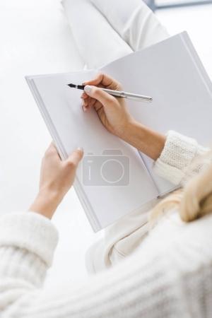 Photo pour Vue recadrée de femme d'affaires en vêtements blancs écrivant dans un cahier - image libre de droit