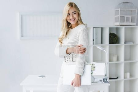 Photo for Smiling businesswoman in white clothes holding laptop in modern light office - Royalty Free Image