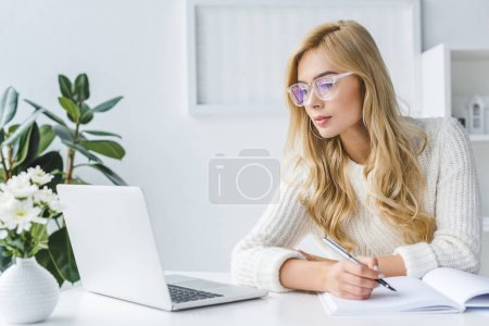 blonde businesswoman writing and workig with laptop