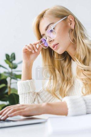 Photo pour Élégante femme d'affaires blonde dans les lunettes à l'aide d'un ordinateur portable dans le bureau de lumière moderne - image libre de droit