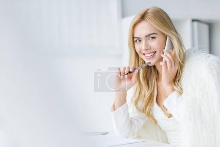 Photo pour Élégante femme d'affaires souriant talking sur smartphone en léger de bureau modern - image libre de droit