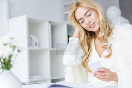 Photo for Happy fashionable businesswoman using smartphone in modern light office - Royalty Free Image