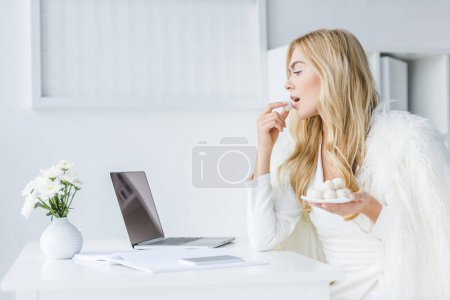 Photo pour Blonde femme d'affaires travaillant avec ordinateur portable et manger blancs friandises en léger de bureau modern - image libre de droit