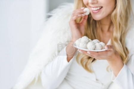 cheerful woman eating candies