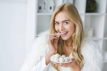 smiling woman eating candies