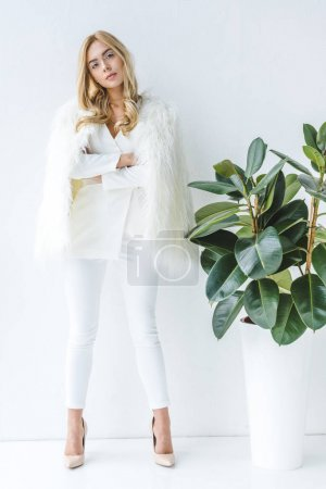 Photo for Fashionable beautiful woman in fur coat posing at ficus plant - Royalty Free Image