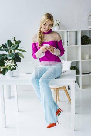 Foto de Elegante mujer de negocios trabajando con smartphone en oficina moderna - Imagen libre de derechos