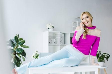 Photo pour Élégante femme d'affaires souriante assise sur la table et parlant sur smartphone dans un bureau moderne - image libre de droit