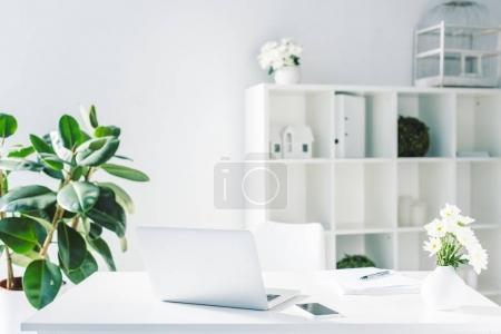 Photo for Light modern office with documents, smartphone and laptop on workplace - Royalty Free Image