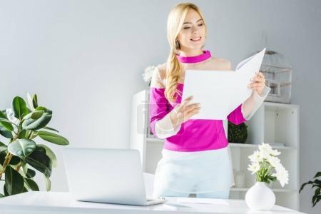 Photo pour Femme d'affaires élégant, travailler avec des documents et ordinateur portable au bureau moderne - image libre de droit