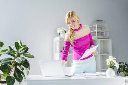 Photo pour Élégante femme souriante travaillent avec des documents et ordinateur portable au bureau moderne - image libre de droit
