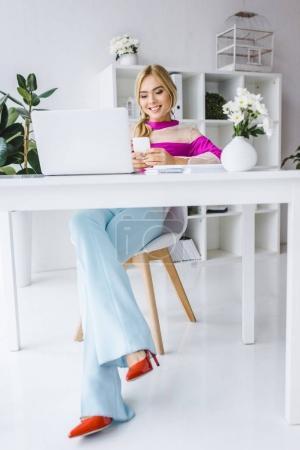 Photo pour Femme d'affaires élégant en jeans évasés, assis au milieu de travail avec ordinateur portable et smartphone - image libre de droit