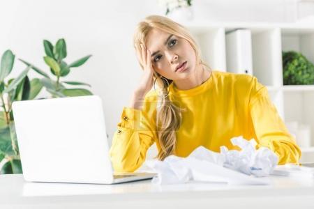 Foto de Empresaria pensativa sentado en el lugar de trabajo con papel arrugado y portátil en la oficina moderna - Imagen libre de derechos