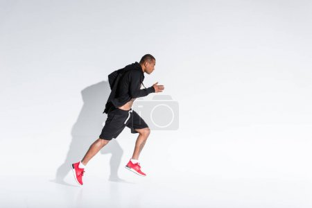 side view of young african american sportsman in sportswear running on grey