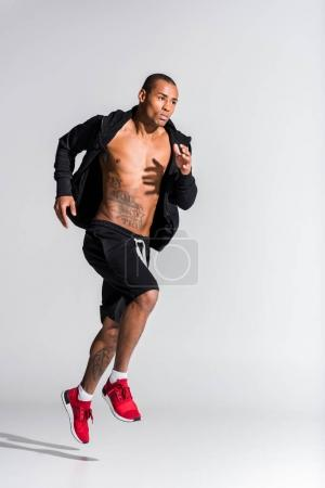 handsome young african american sportsman running on grey