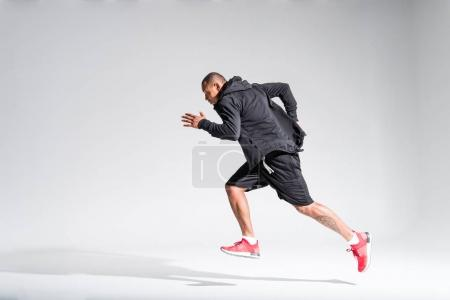 side view of young african american sportsman running on grey