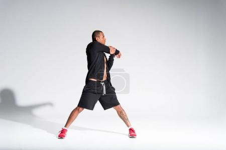 full length view of young athletic african american sportsman stretching on grey