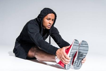 young african american sportsman in sneakers stretching legs on grey