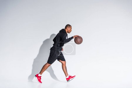 side view of young african american sportsman playing with basketball ball on grey