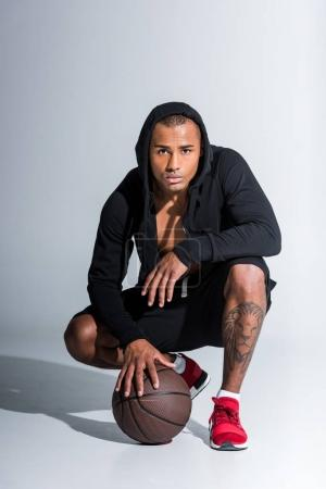 Photo pour Sportif afro-américain accroupi avec ballon de basket et regardant la caméra sur fond gris - image libre de droit