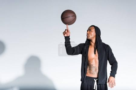 african american man holding basketball ball on finger on grey