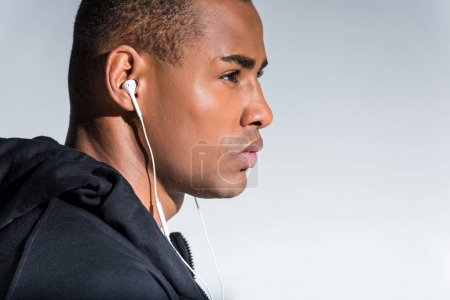 profile portrait of young african american man listening music in earphones and looking away  isolated on grey