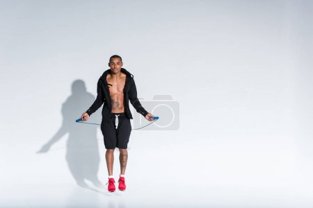 young african american sportsman exercising with skipping rope and looking at camera on grey