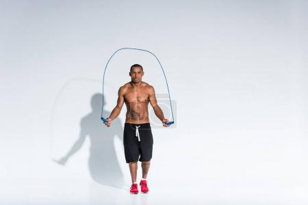 shirtless african american sportsman exercising with skipping rope on grey