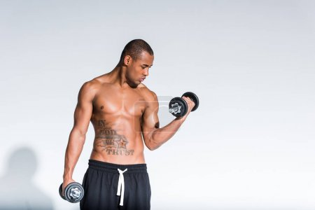 athletic young shirtless african american sportsman training with dumbbells isolated on grey