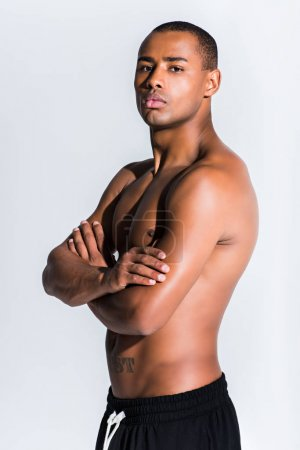 portrait of handsome shirtless african american sportsman standing with crossed arms and looking at camera isolated on grey