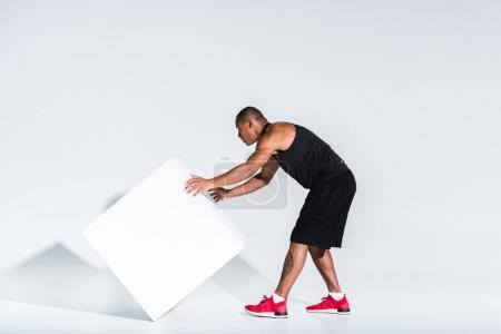 Photo for Young african american sportsman moving white cube on grey - Royalty Free Image