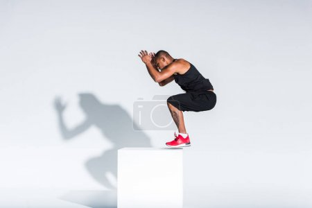 Photo for Side view of young african american sportsman exercising on grey - Royalty Free Image
